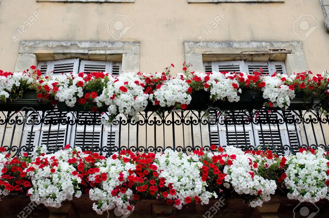 Rote Und Weisse Blumenanzeige Auf Einem Balkon Lizenzfreie Fotos