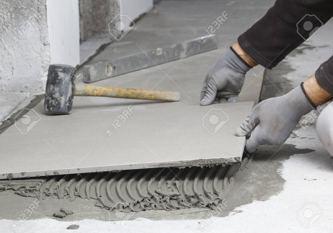 Home Improvement Renovation Construction Worker Tiler Is Tiling - Ceramic tile cutting service