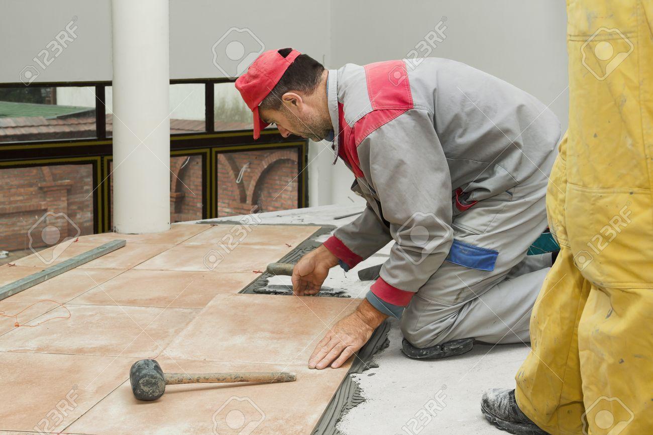 Home improvement renovation construction worker tiler is tiling home improvement renovation construction worker tiler is tiling ceramic tile floor adhesive dailygadgetfo Gallery