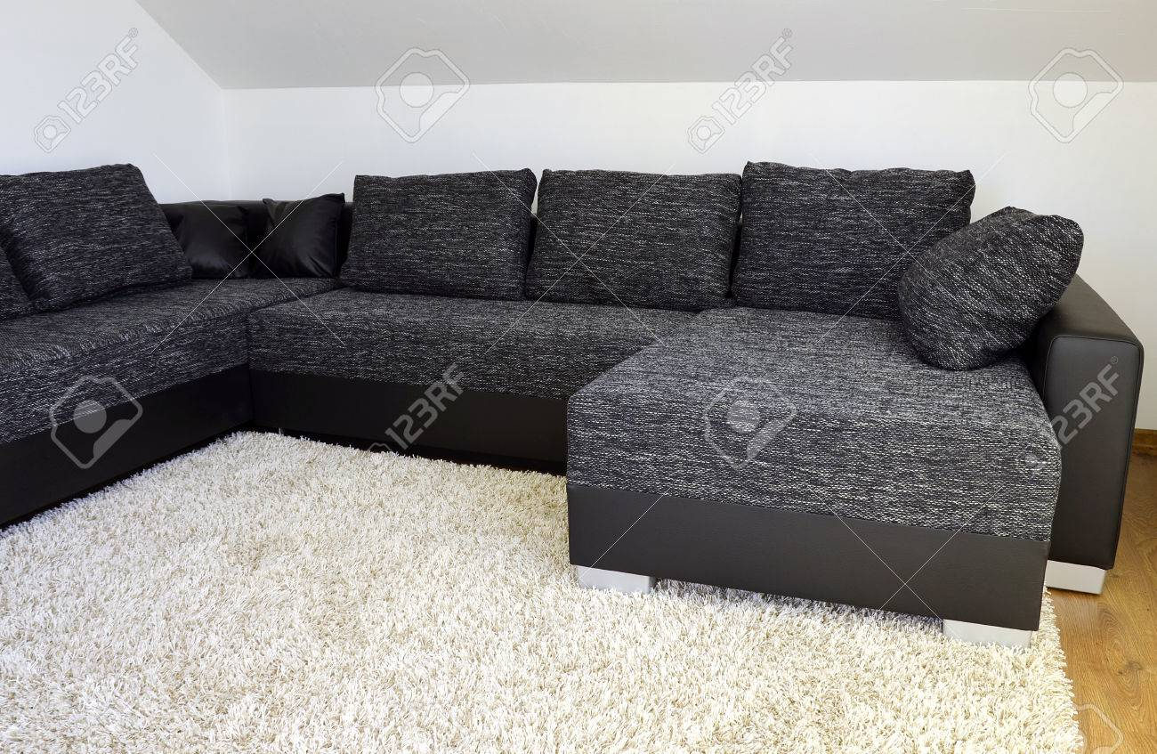 Modern black and white cloth sofa with black leather and pillows..
