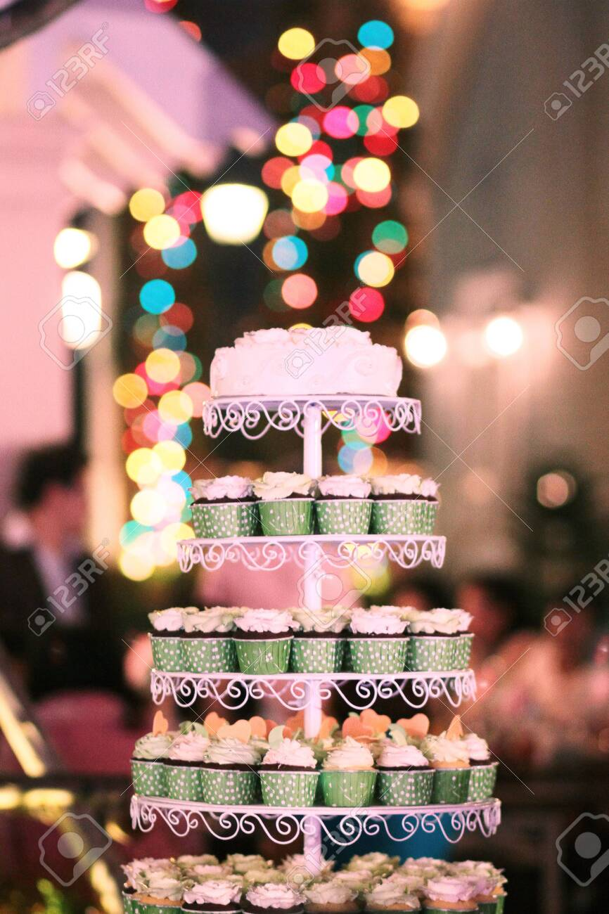 Wedding Cupcakes with colorful sprinkles in green cup with garland lights bokeh background - 149943625