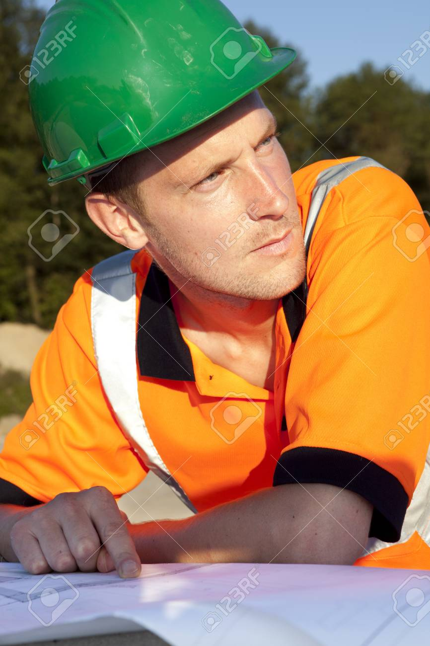 Man is looking away and pointing at blueprint Stock Photo - 12155360