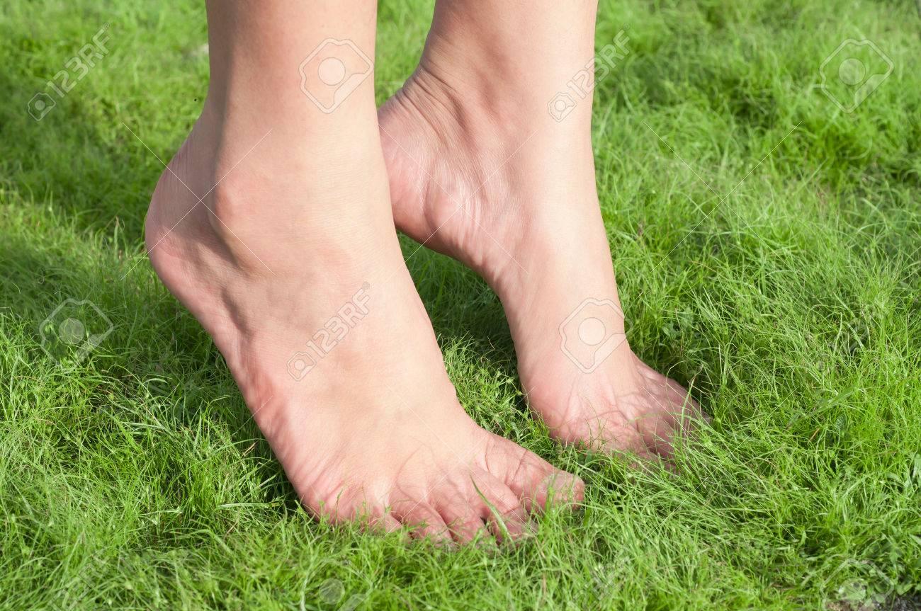 Woman feet tiptoe over green grass. - 37259377