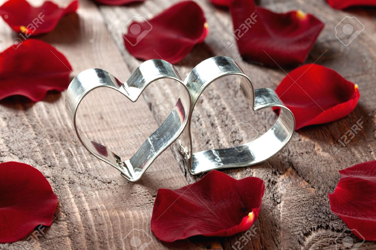 Two Hearts With Petals On Wooden Table Stock Photo Picture And
