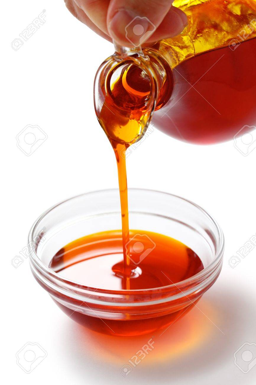 pouring red palm oil into a glass bowl Stock Photo - 14960502