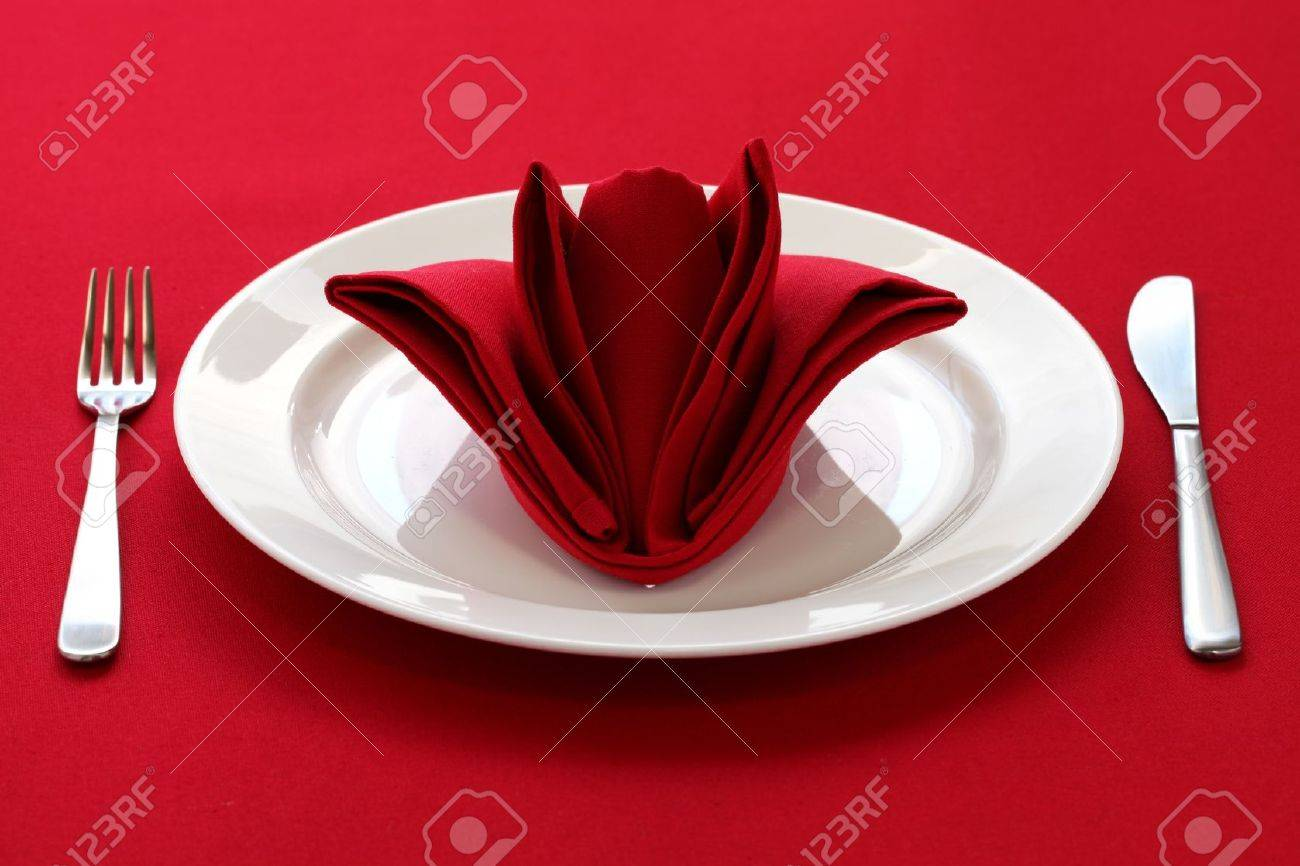 Table Setting Background folded napkin like a rose bud, table setting on red background