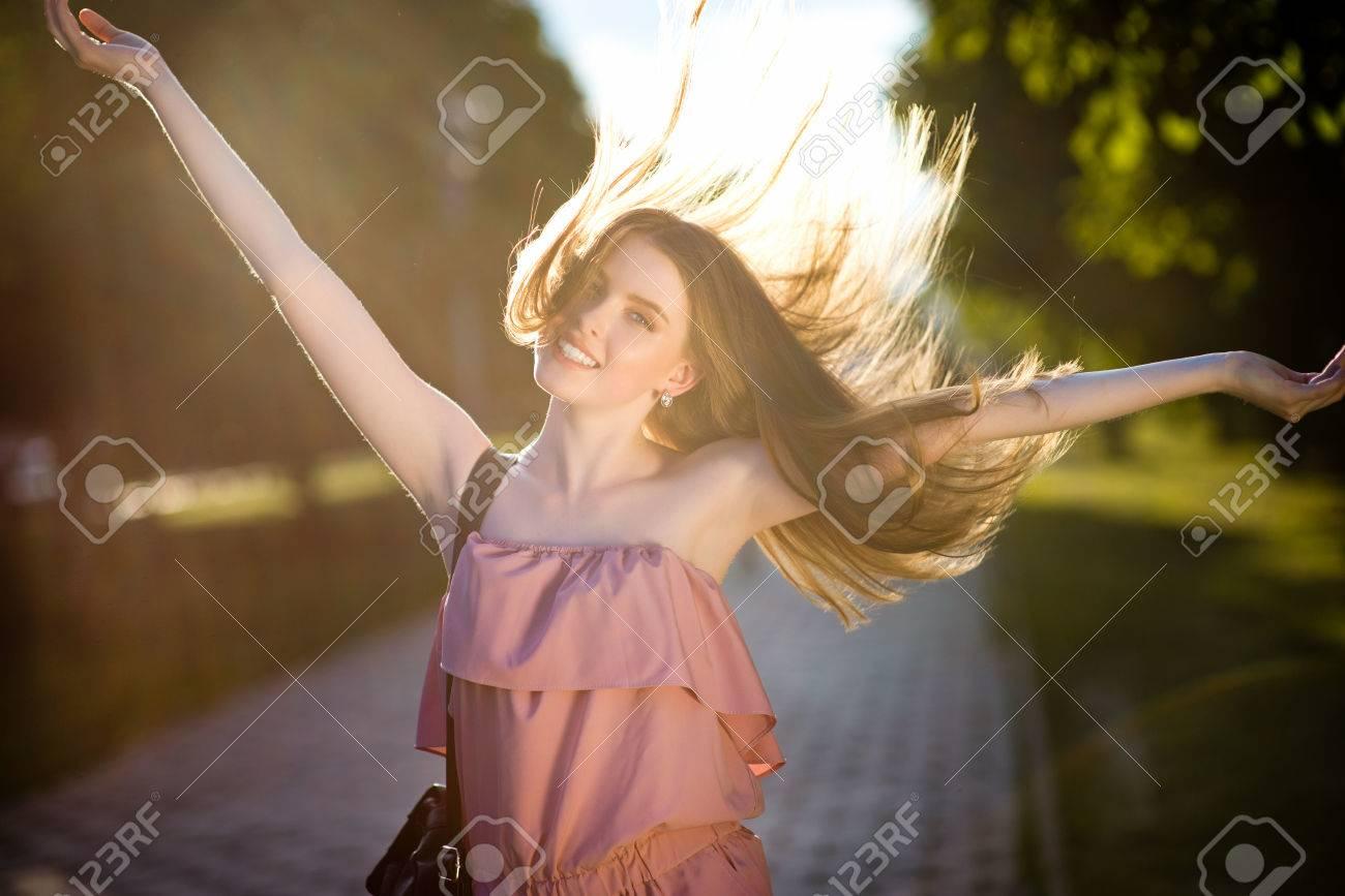 5d175055302b Archivio Fotografico - La giovane bella ragazza alla moda vestita con bei  capelli sta camminando lungo le vie della città al tramonto