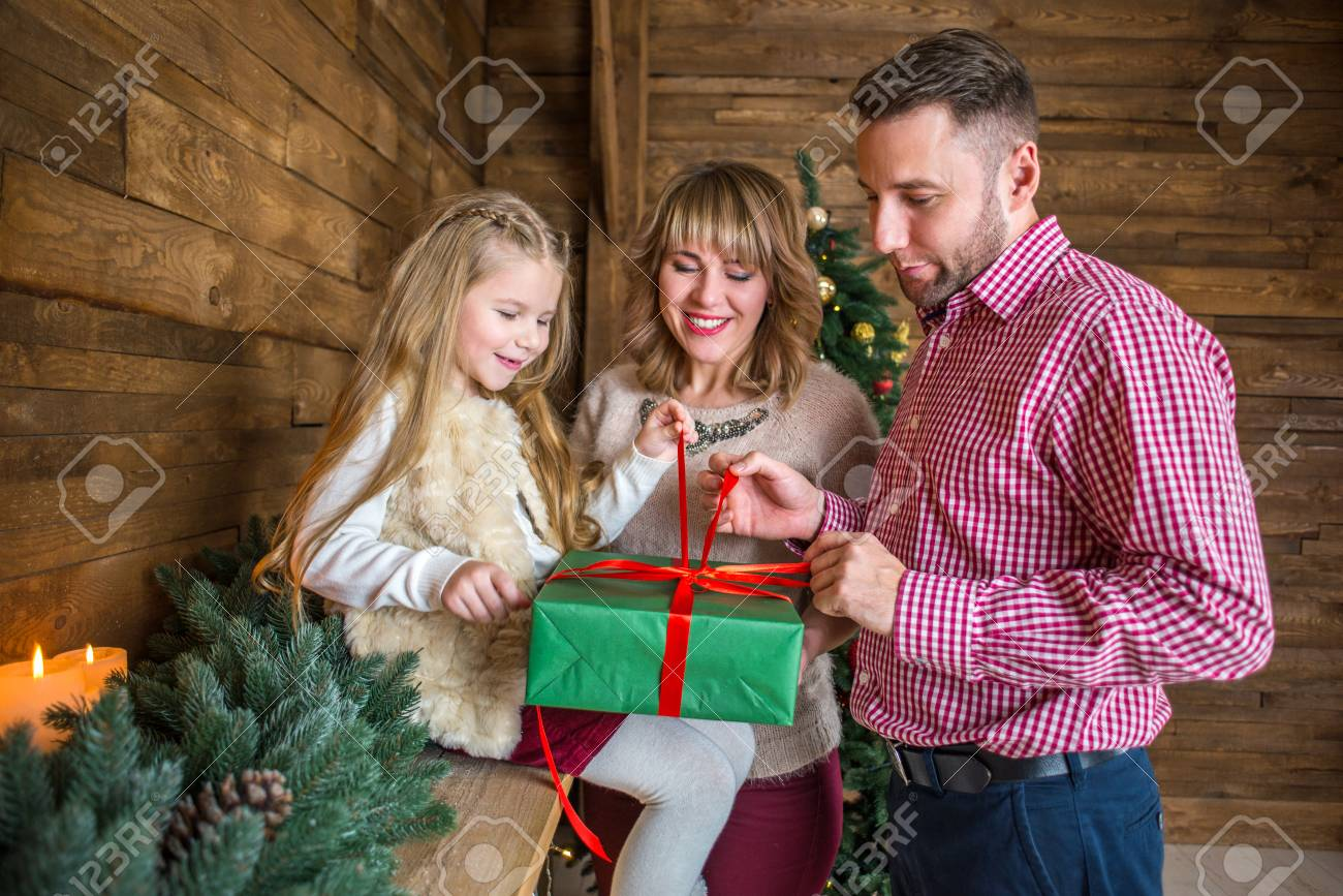 Family Mom Dad And Daughter On The Eve Of Christmas Give Each Stock Photo Picture And Royalty Free Image Image 92123307