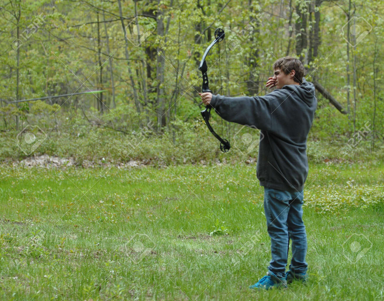 ef486cd0c5db teenage boy shooting compound bow with arrow in the scene Stock Photo -  4992929