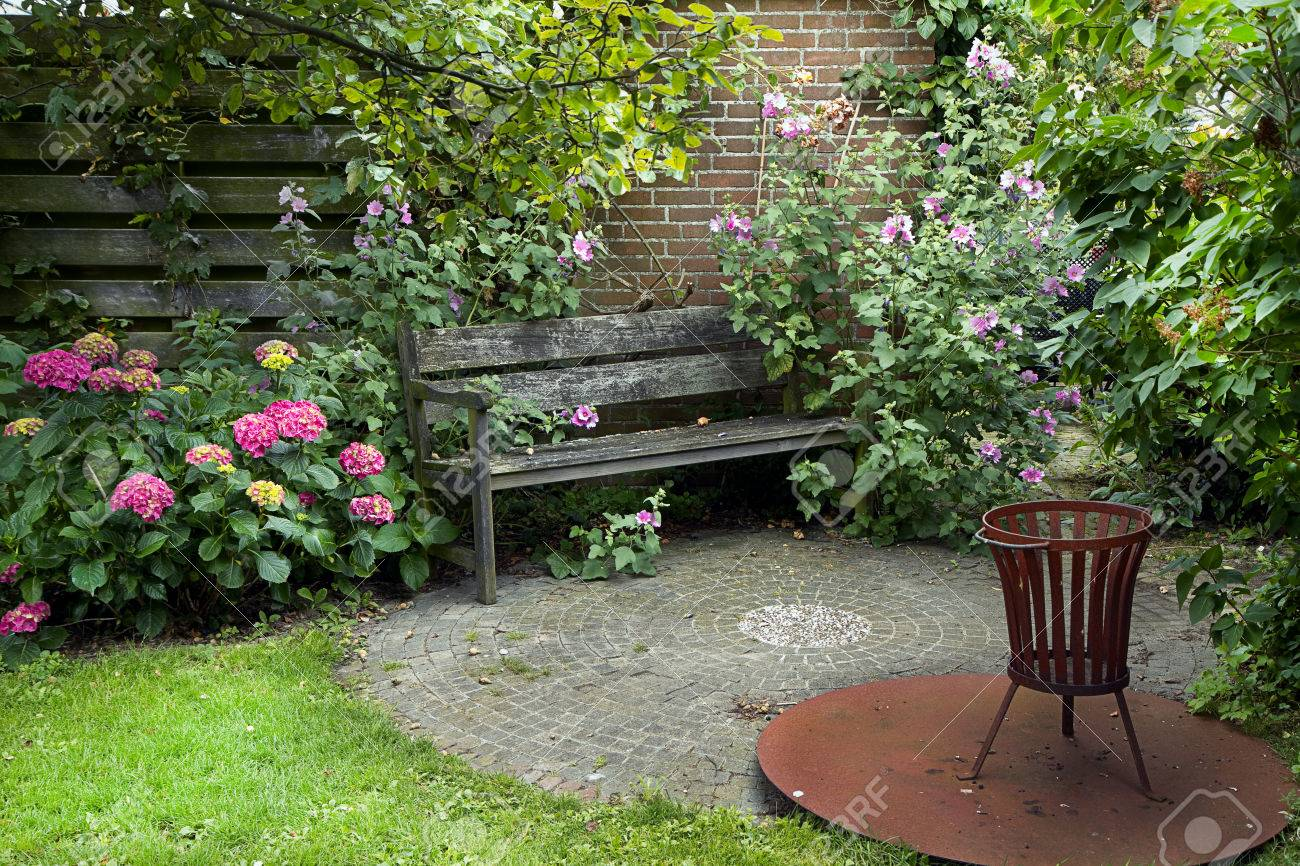 country style garden with bench fireplace and lots of flowers