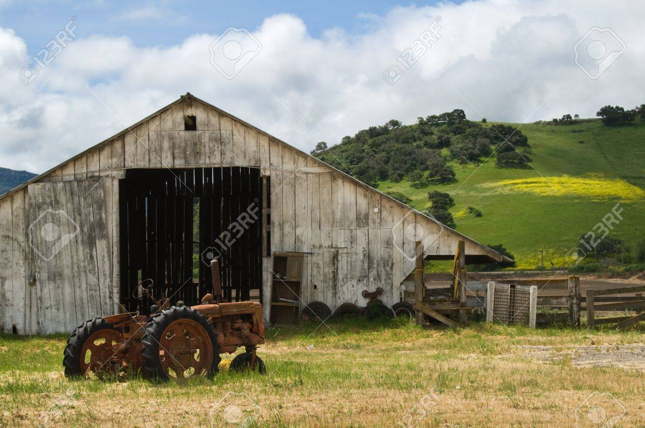Old wooden barn with rusted tractor sitting out front. Stock Photo - 9920007