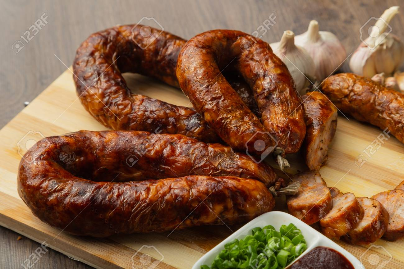 Homemade sausage on a wooden background with seasonings and sauce. Stock Photo - 104821365