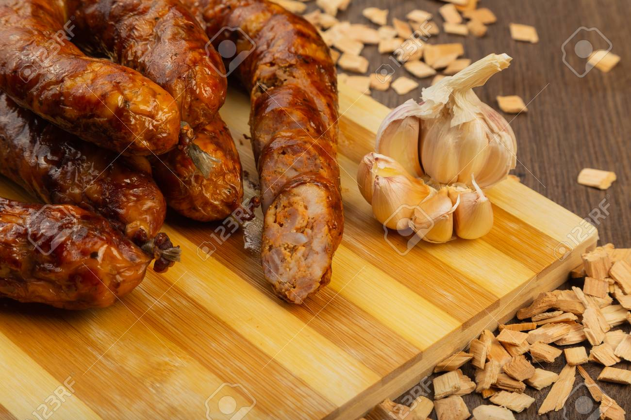 Homemade sausage on a wooden background with seasonings and sauce. Stock Photo - 104821425