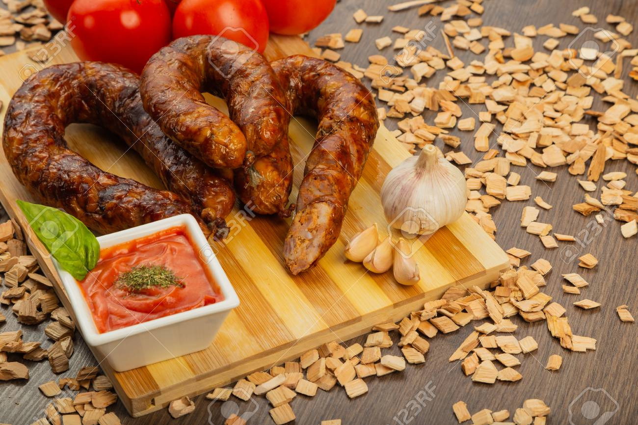 Homemade sausage on a wooden background with seasonings and sauce. Stock Photo - 104821438