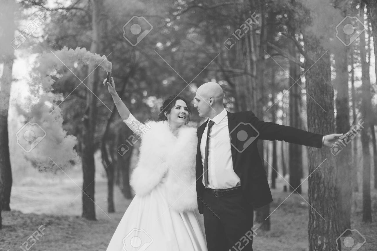 Happy bride and groom hold colored smoke in their hands. - 139112193