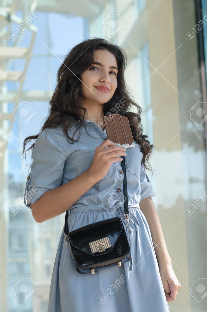 new styles 6f192 66999 Donna in possesso di una tavoletta di cioccolato. Lei è vestito con una  camicia di jeans blu e lei ha i capelli lunghi scuri.