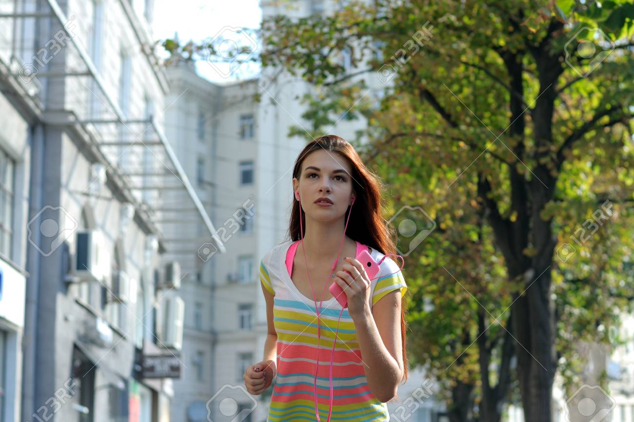 4970a8ef Girl running down the street early in the morning in the city and listening  to music through headphones. She has long red hair, she is wearing a  striped ...