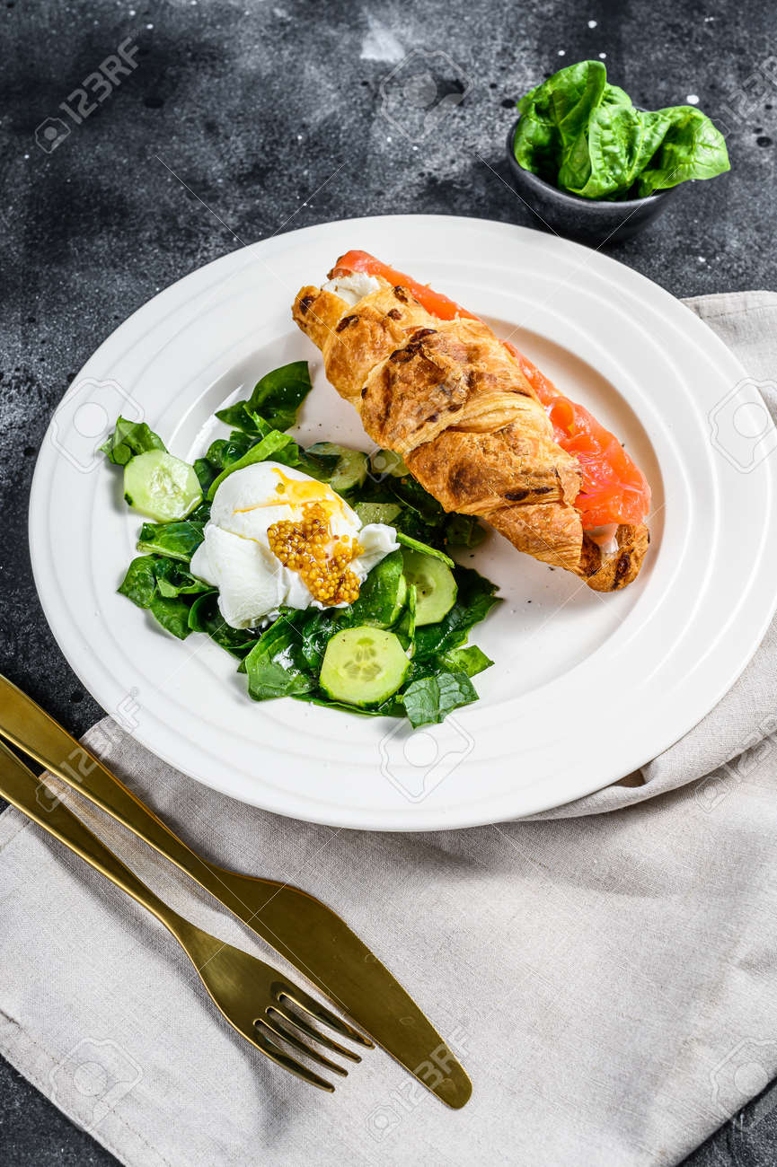 Croissant sandwich with salted salmon served with fresh salad leaves spinach, egg and vegetables. - 146052257