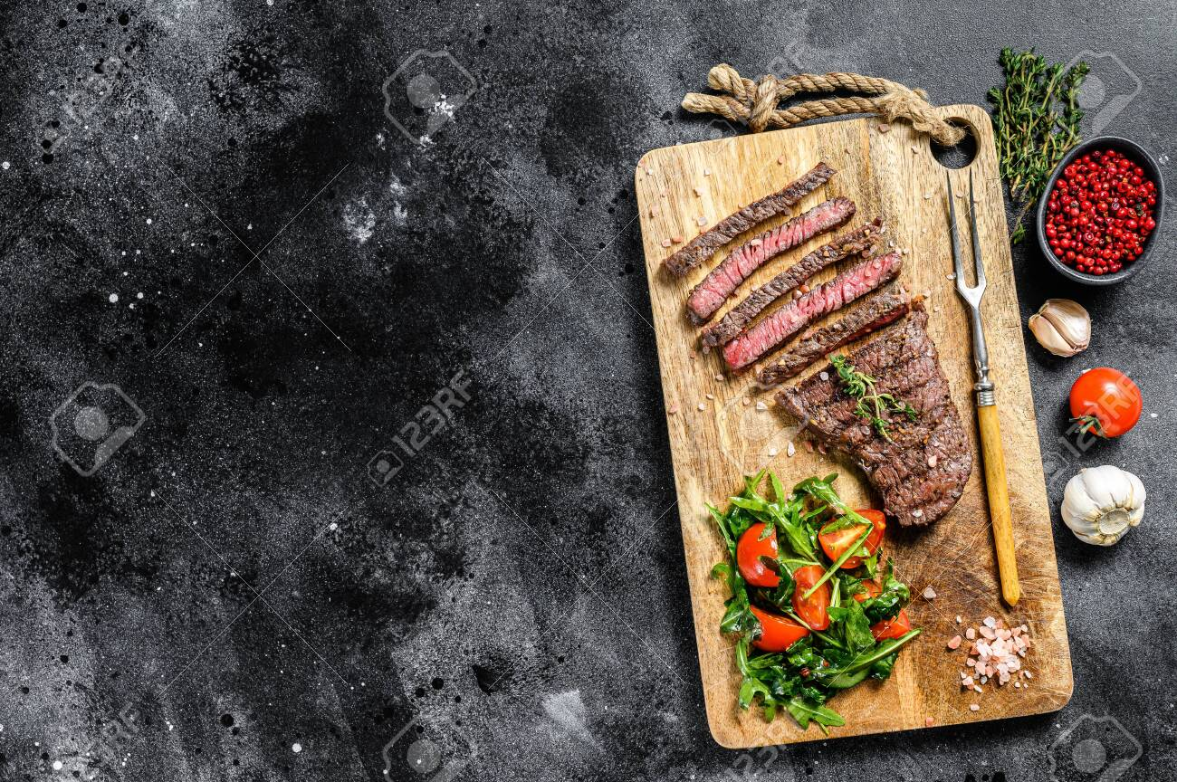 Grilled sliced Denver steak on a cutting board. BBQ beef. Black background. Top view. Copy space. - 149453739