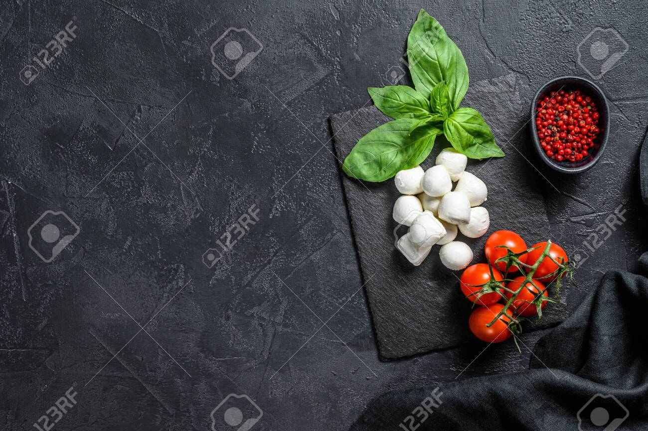 Mini mozzarella cheese, Basil leaves and cherry tomatoes, cooking Caprese salad. black background. top view. Copy space. - 149434692