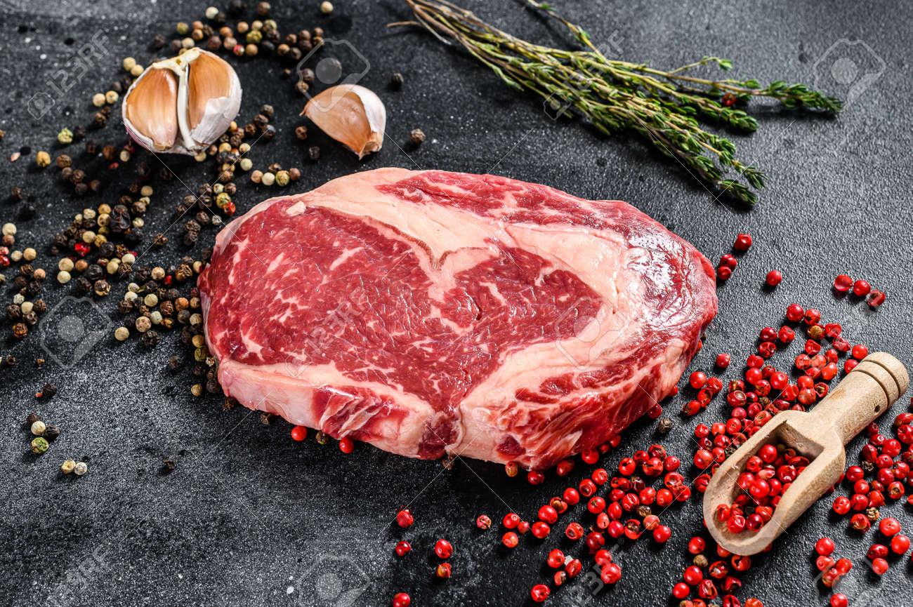 Raw fresh marbled meat Steak Ribeye. Black Angus Rib eye with cooking ingredients. black background. top view. - 156171594
