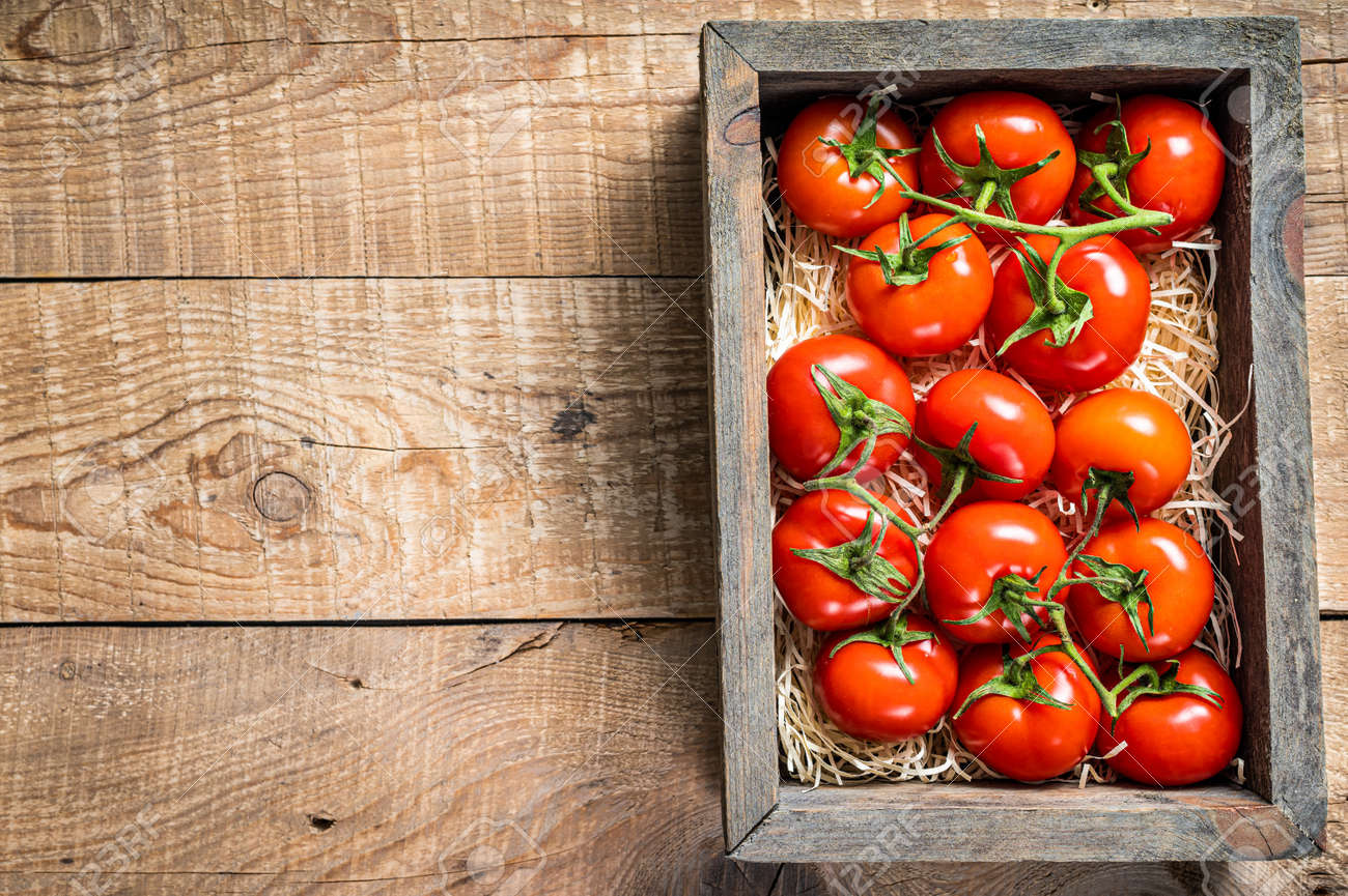 Red tomatoes in wooden market box. Wooden background. Top view. Copy space - 165999707