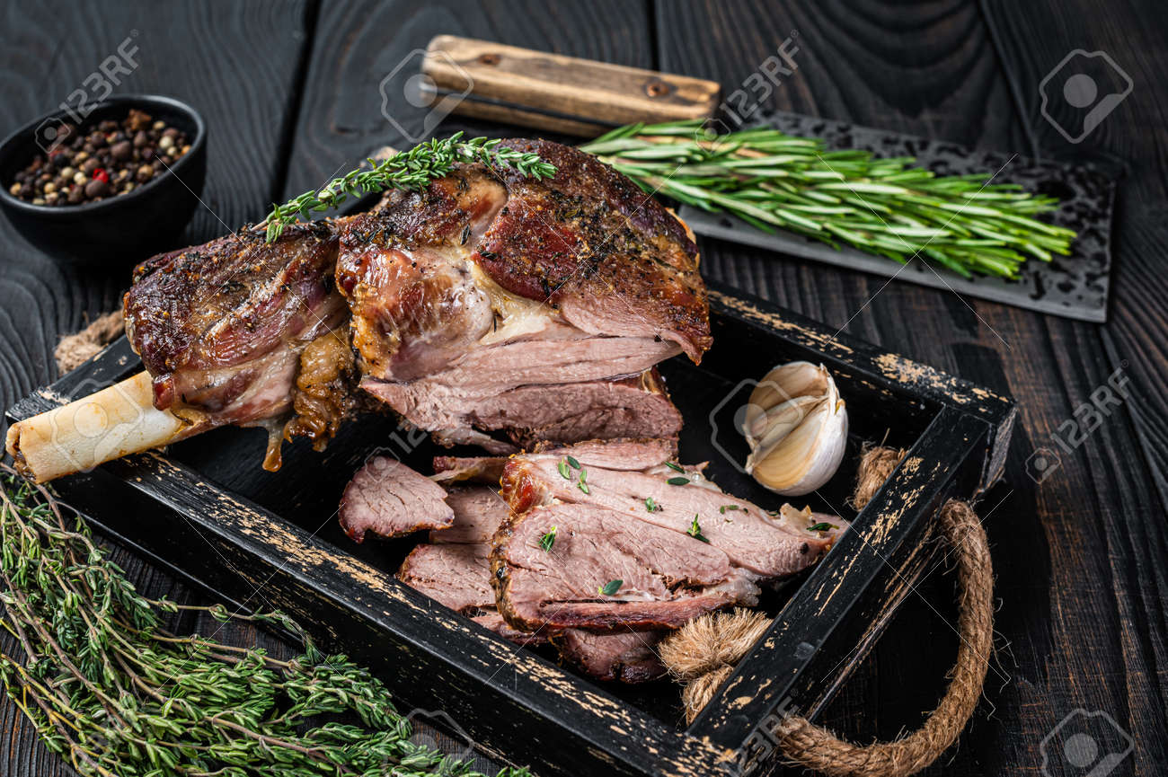 Roasted mutton lamb leg sliced in a wooden tray with meat cleaver. Black wooden background. Top view - 166979315