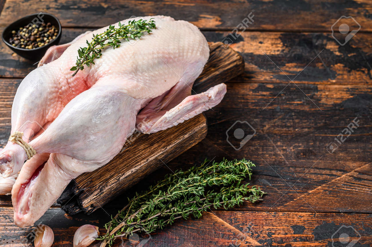 Raw whole mallard duck, poultry meat with herbs. Dark wooden background. Top view. Space for text - 168990843
