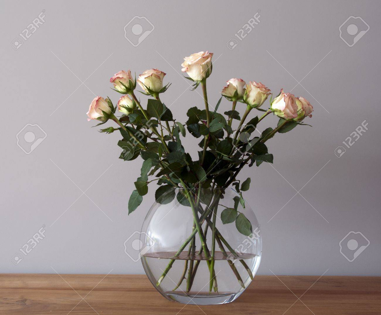 bouquest of roses in a vase on wooden table - 13306880