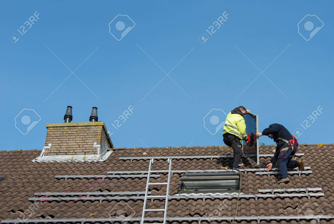 man putting the solar panel to the metal construction on the roof - 25983629