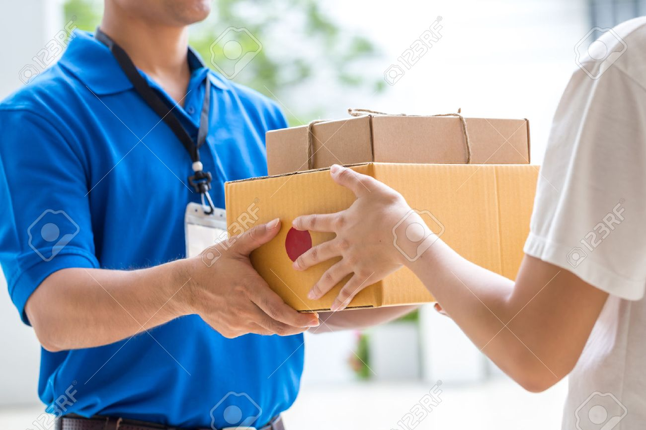Woman hand accepting a delivery of boxes from deliveryman - 52450552