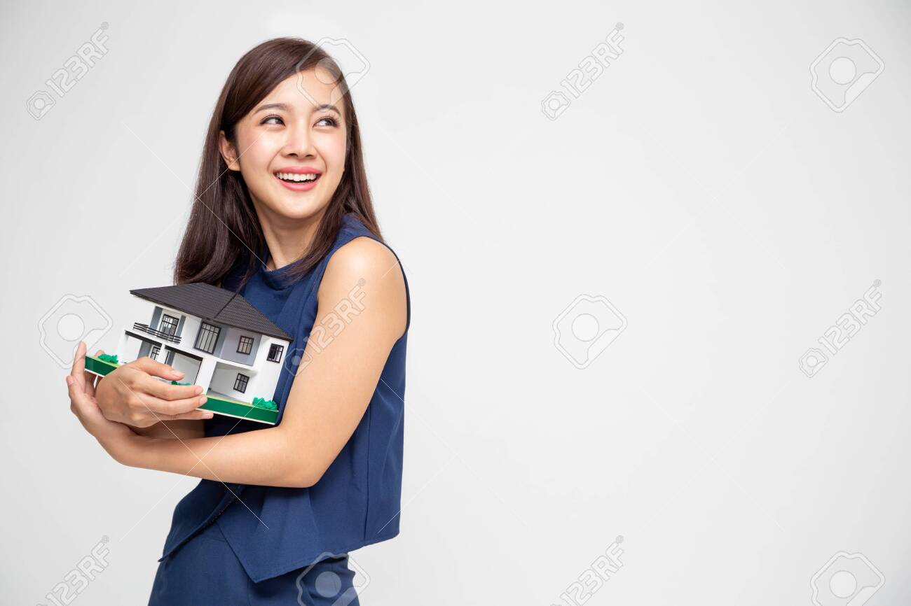 Young Asian woman smiling and hugging dream house sample model isolated over white background, Real estate and home insurance concept - 128756320