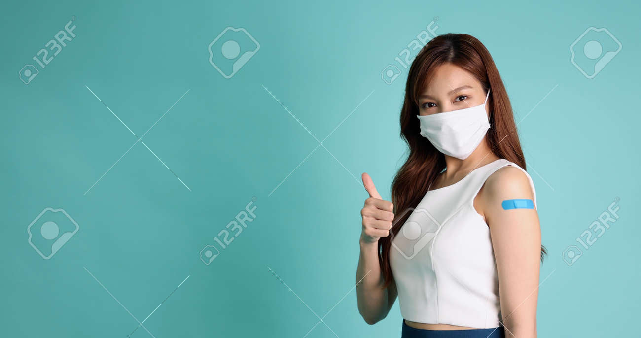 Beautiful Asian woman wearing face mask and showing thumbs up and arm with plaster or bandage of Vaccinated isolated on green background - 173264207