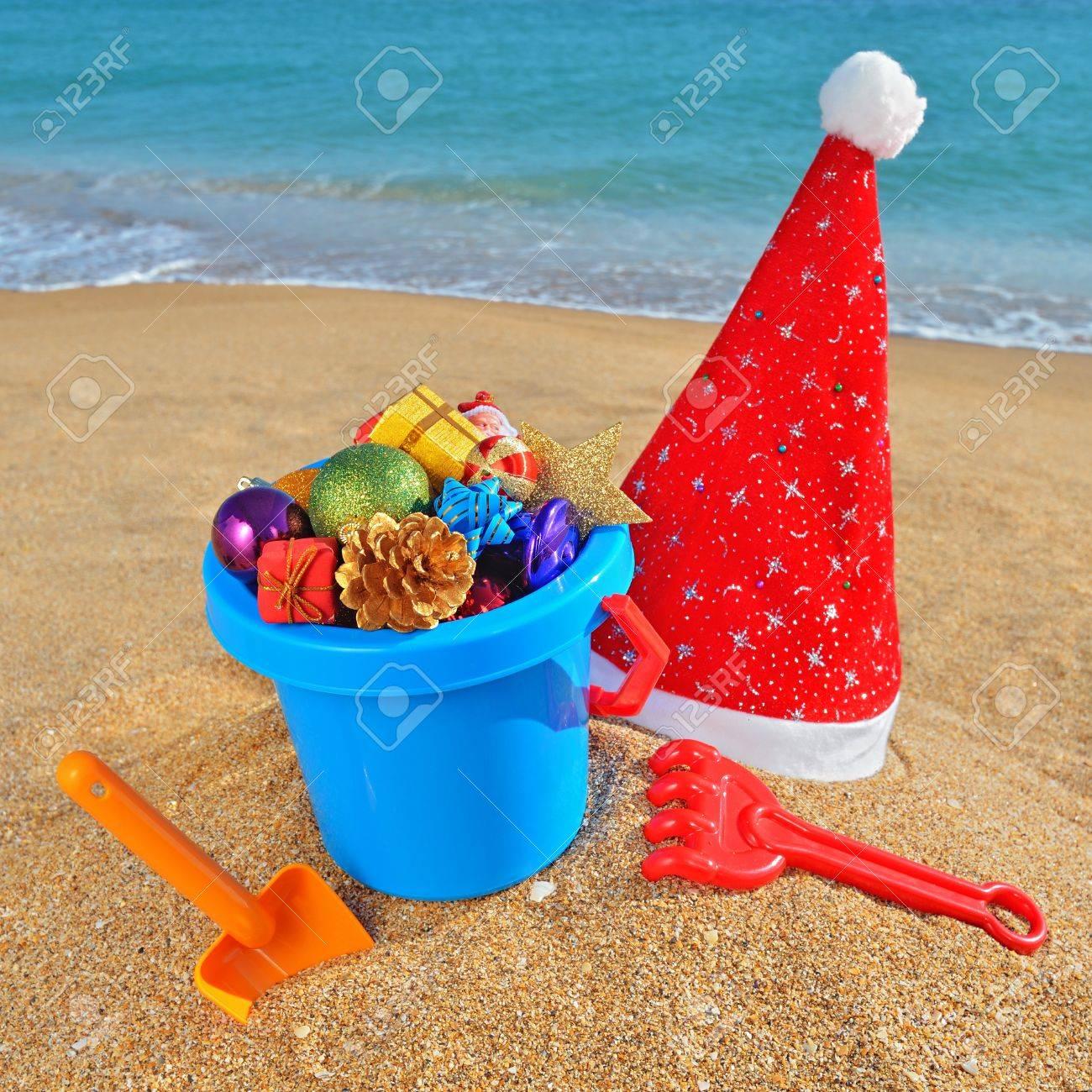 Christmas toys, decorations and Santa Claus cap on the beach against a blue ocean Stock Photo - 16167514