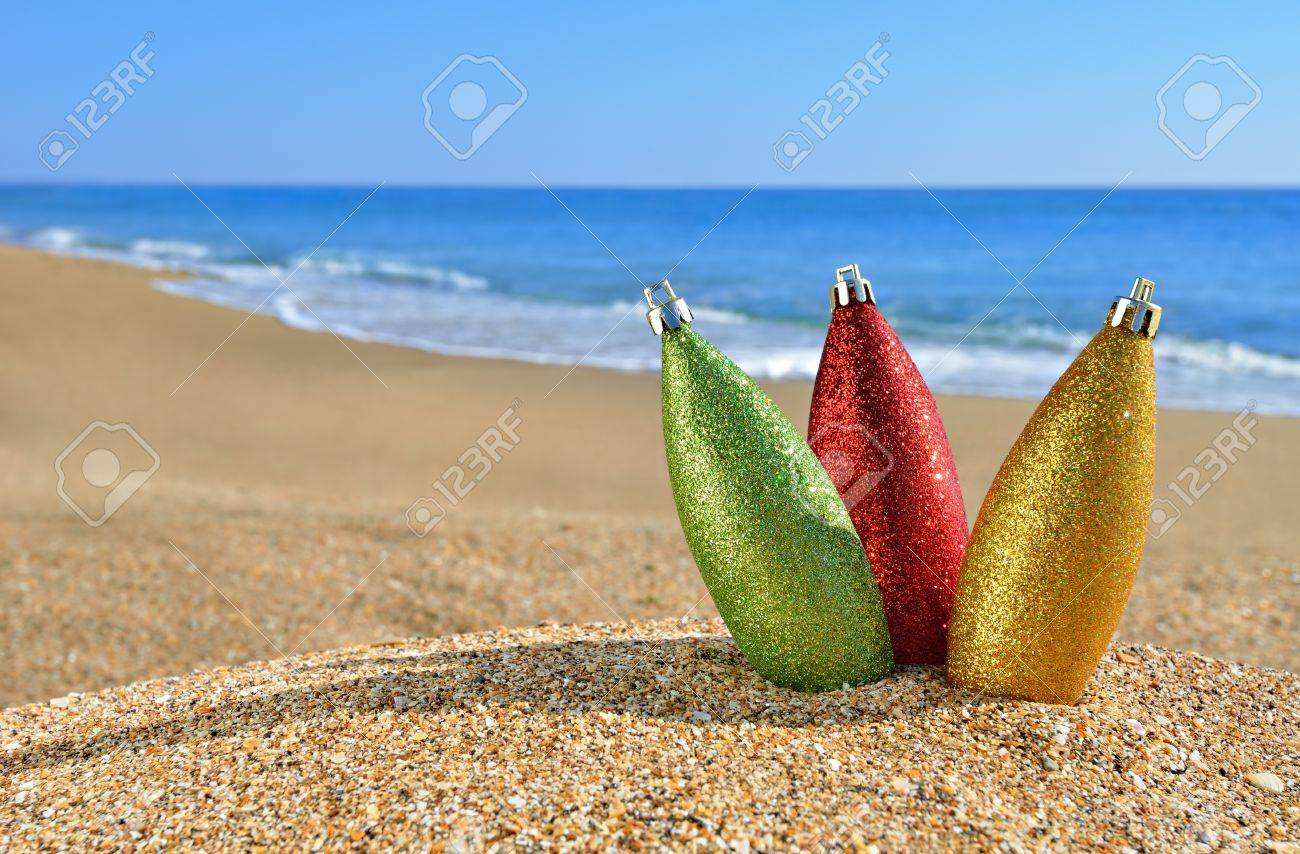 Christmas decorations on yellow beach sand against blue ocean - 16167519