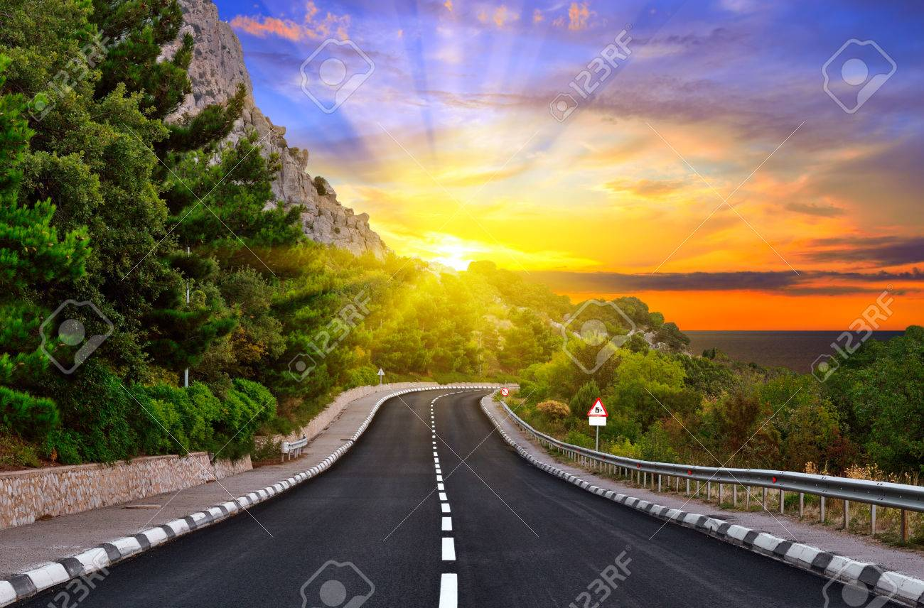Highway against mountains and a dramatic sunset - 27724828