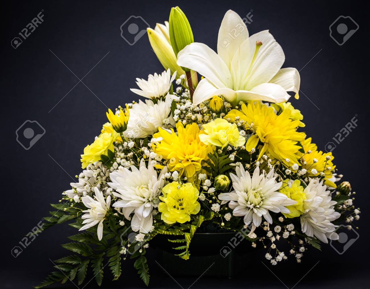 A Bouquet Of Yellow And White Flowers Set On A Black Background