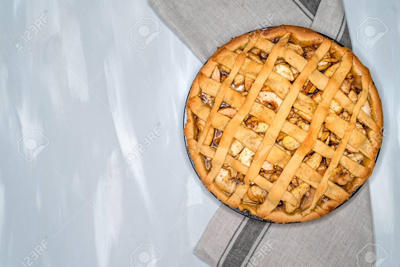 Apple pie tart with raisins, nuts and cinnamon on vintage wooden background texture. Traditional dessert for Independence Day in America. Rustic style. Top view - 89751940