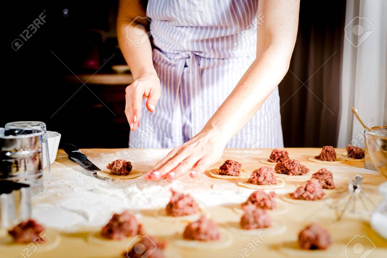La mujer hace albóndigas en casa en la mesa de la cocina