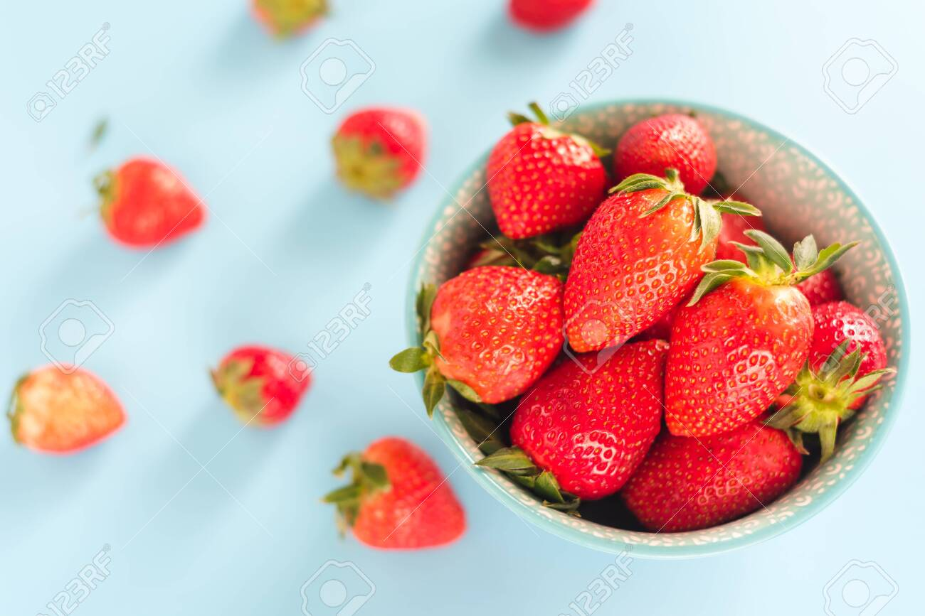 Juicy, ripe strawberries in a colorful turquoise bowl, top view - 128261188