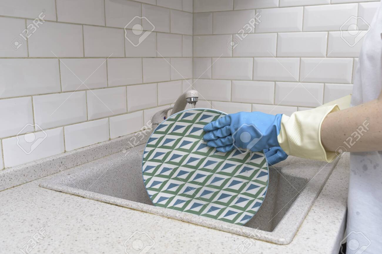 Woman washes dishes. Washing dishes - hands with gloves in kitchen, housework - 151138780