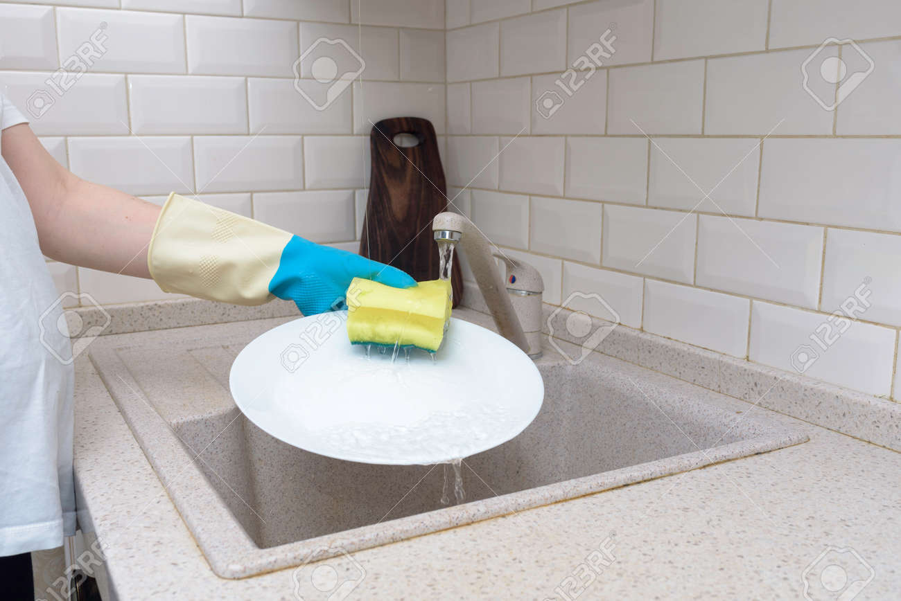 Woman washes dishes. Washing dishes - hands with gloves in kitchen, housework - 151865764