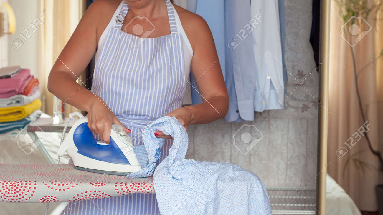 young beautiful woman ironing clothes on ironing board. Housework - 151865778