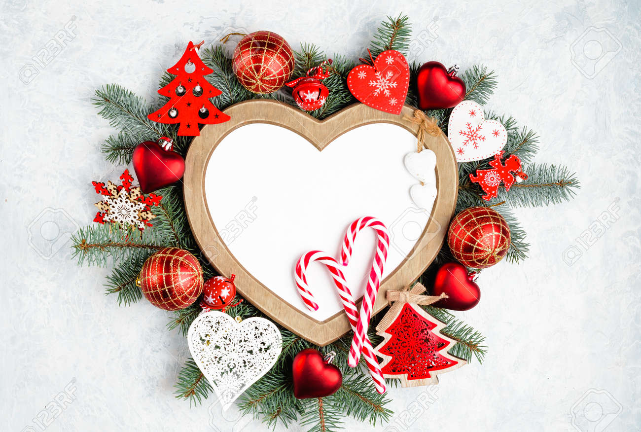 Christmas frame in the shape of a heart is surrounded by branches of a New Year tree Christmas decorations with copy space. Top view, flat lay. Nature New Year concept. - 151814802