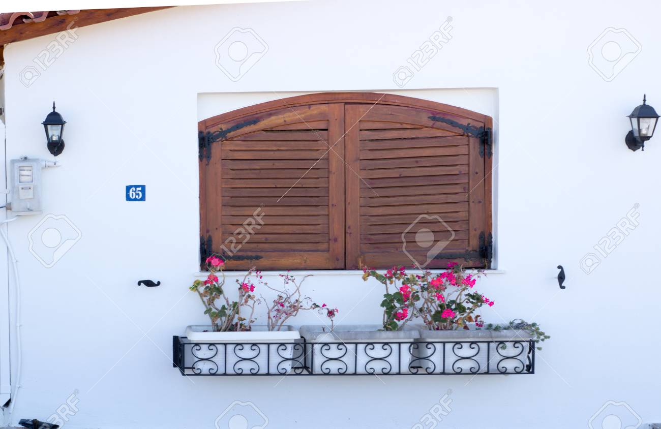 The Exterior Of A Small Beautiful House With A Window With Closed