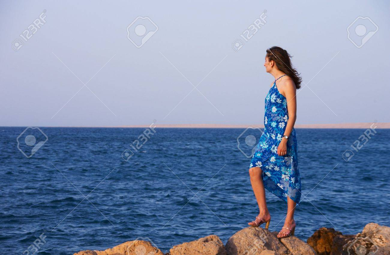 The girl in a blue dress standing on a stone and looking at the sea Stock Photo - 1157075