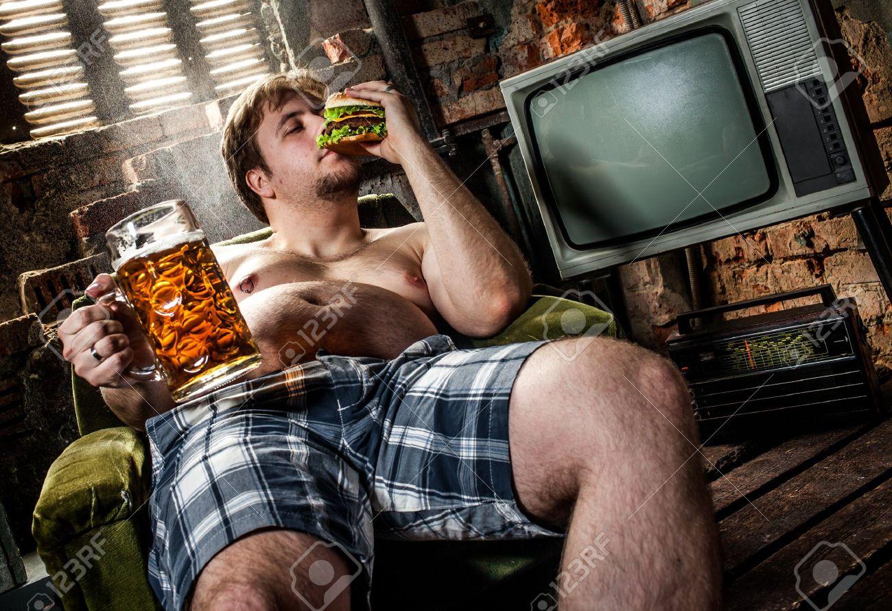 fat man eating hamburger seated on armchair Stock Photo - 13109556