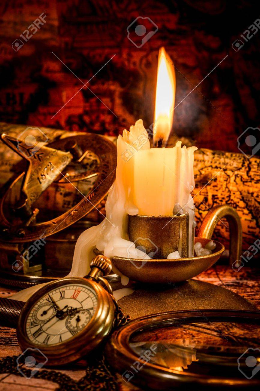 Vintage compass, pocket watch lie on an old ancient map with a lit candle Stock Photo - 19447709