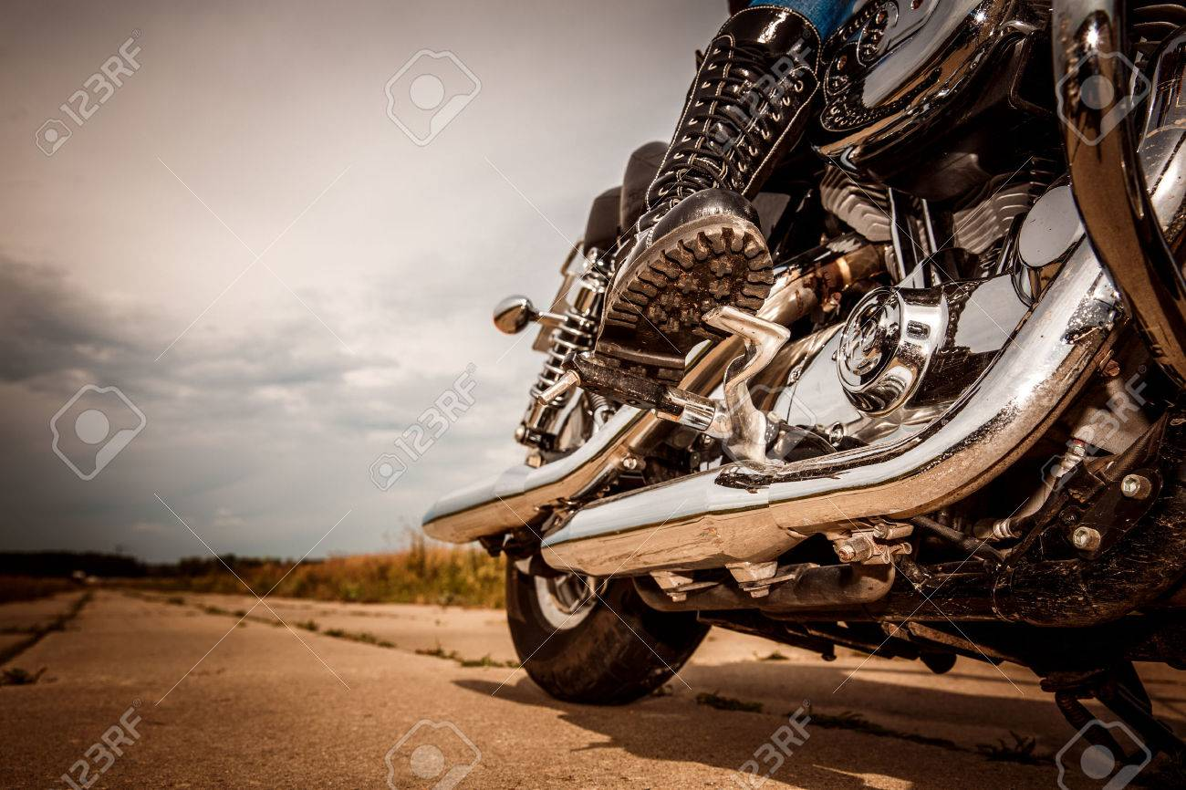 Biker girl riding on a motorcycle. Bottom view of the legs in leather boots. - 51825913