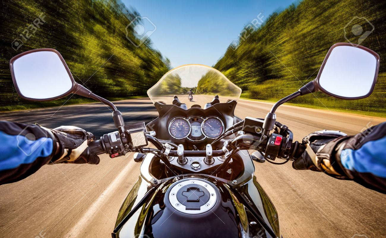 Biker driving a motorcycle rides along the asphalt road. First-person view. - 54766213